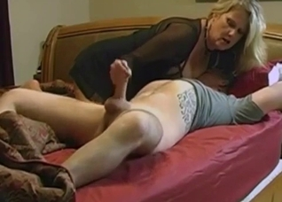 Blonde MILF jerks off her son's dick in the bed